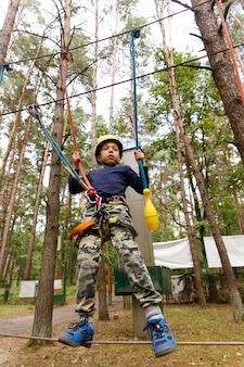 Little boy in helmet spend his leisure time in adventure playground.