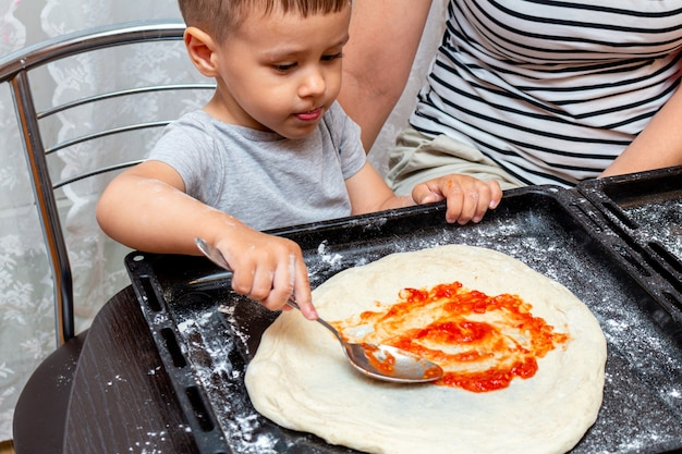 ママが家でピザを作るのを助ける小さな男の子