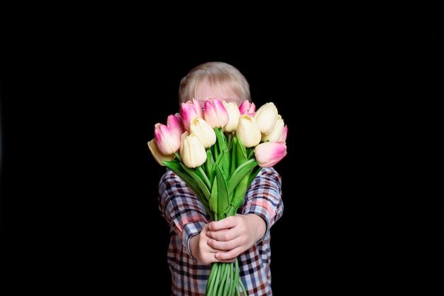 Little boy hides his face behind a bouquet of tulips as gift for mothers day