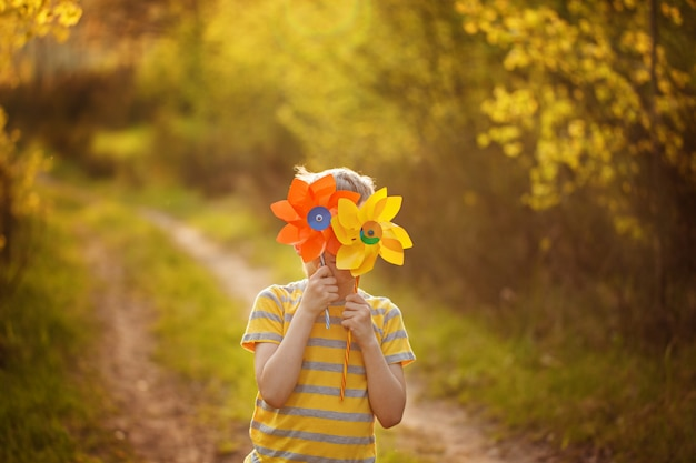 Little boy hides behind yellow and orange pinwheels on green forest background in sunny day.