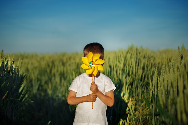 Little boy hides behind yellow pinwheel on blue sky