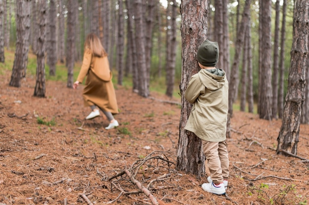 Little boy hiding from his mother in the forest