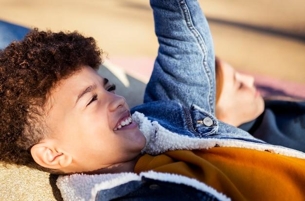 Маленький мальчик, пряча лицо от солнца на открытом воздухе
