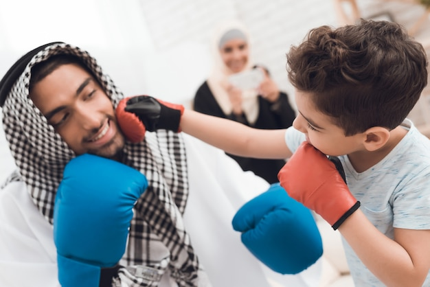 Little boy and his father in clothes train in boxing gloves.