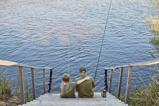Little boy and his father fishing together while sitting near water on wooden stairs, son hugging his father with hand, family posing with fishing rods.