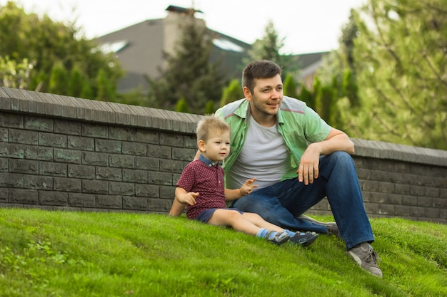 Little boy and  his father  sit on green grass. concept of father's day! happy family dad and child