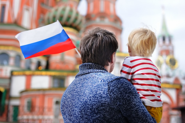 Little boy and his middle age father holding russian flag with saint basil's cathedral