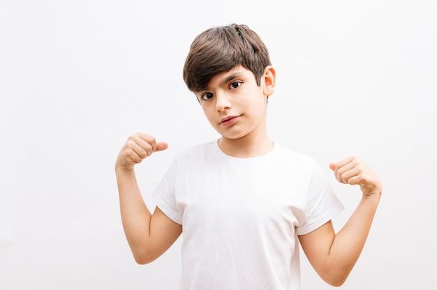 작은 소년 히스패닉 아이 캐주얼 흰색 tshirt 입고 매우 행복 하 고 팔 승자 제스처를 하 고 흥분 웃 고 성공을 위해 비명. 축하 개념.