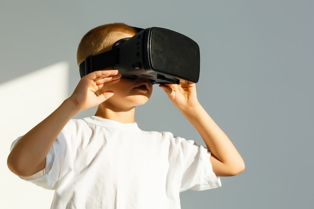 Little boy holdg his hand to virtual reality 3d glasses on his head and looking up smiling