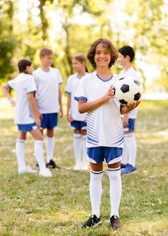 Маленький мальчик держит футбольный мяч на улице рядом с другими детьми