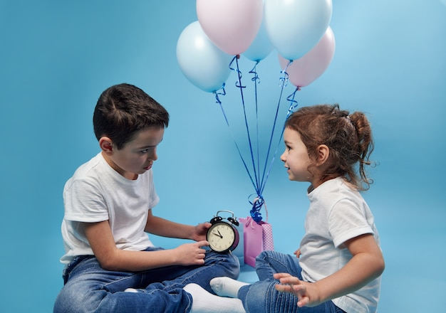 Little boy holding an alarm clock and showing it to his sister on the surface of colored balloons