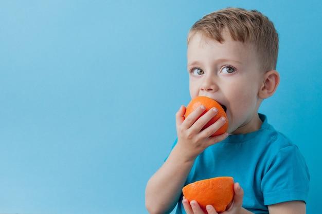 青い背景、ダイエット、健康の概念のための運動にオレンジを手に持っている小さな男の子。