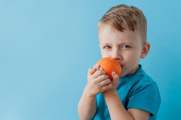 Маленький мальчик держит апельсин в руках
