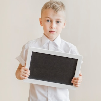 Little boy holding blackboard in studio