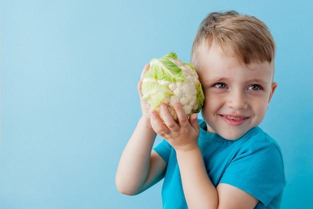 青い背景、ダイエット、健康コンセプトのための運動でブロッコリーを手に持っている小さな男の子。