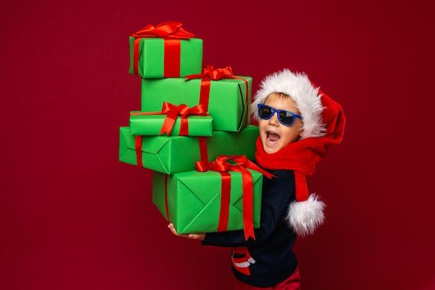 Маленький мальчик держит рождественские подарочные коробки