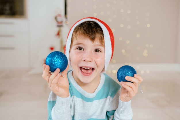 Little boy holding christmas ornaments