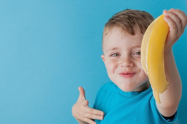 Little boy holding and eating an banana on blue wall, food, diet and healthy eating concept