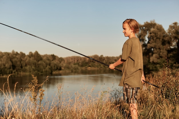 Little boy holding fishing pole in hands, wearing green t shirt and cap, blond male kid fishing at bank of river, looks concentrated, wants to catch fish.