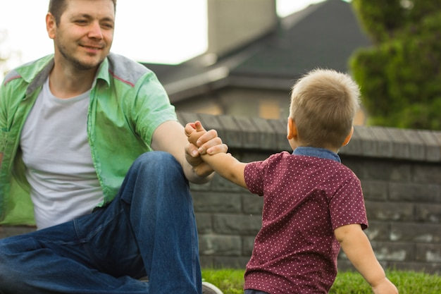 Little boy holding the hand of his father. concept of father's day! happy family dad and child