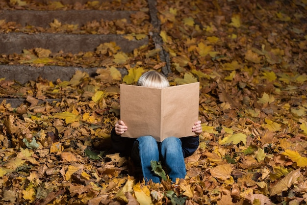 Little boy holding large book in hands and sitting on fallen autumn leaves. child loves to read.