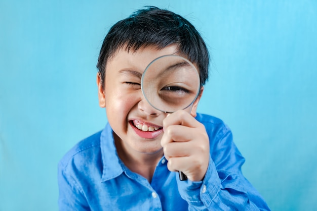 Little boy holding magnifying glass