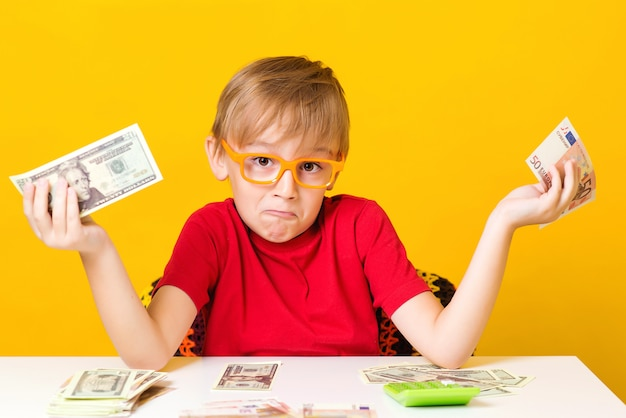 Little boy holding money and thinking about new business start up. small professor in eye glasses with cash over yellow background