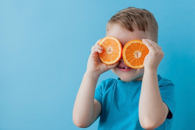 Little boy holding an orange in his hands on blue