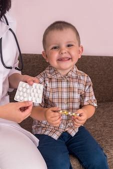 Маленький мальчик, держа в руках таблетки в блистере