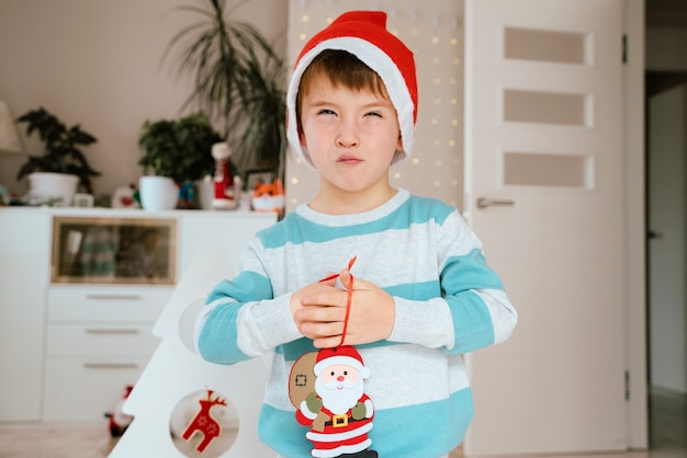 Little boy holding a santa claus ornament for christmas decoration