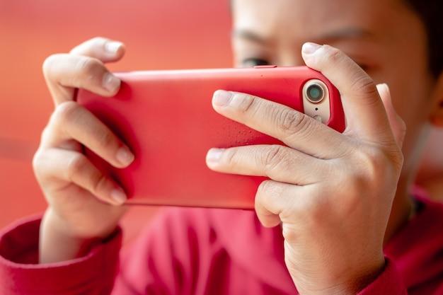 Маленький мальчик, держащий смартфон в горизонтальном положении. малыш играет в игры, серфинг в интернете, обучение.