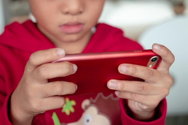 Маленький мальчик держит смартфон в горизонтальном положении