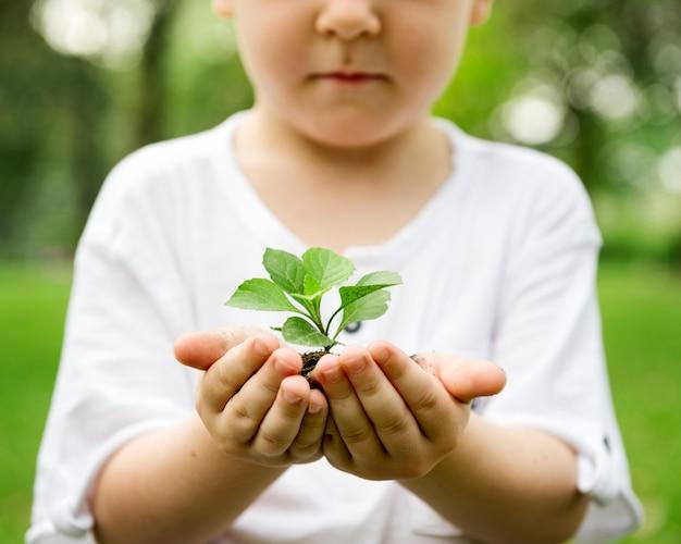 공원에서 흙과 식물을 들고 어린 소년