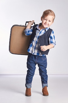 Little boy holding suitcase going vacation travel