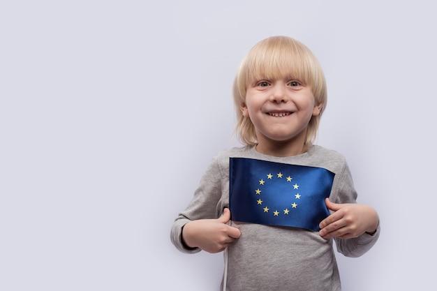 Маленький мальчик держит флаг европейского союза