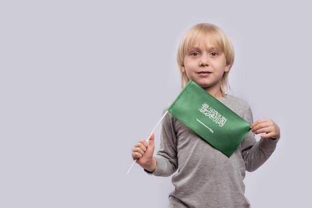 Маленький мальчик держит флаг саудовской аравии