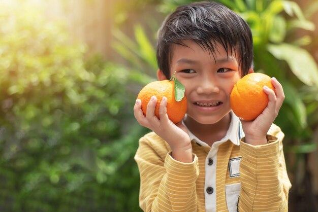 Little boy holding two big fresh mandarin oranges fruits in organic farm agriculture