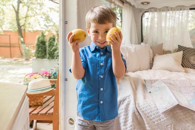 2つのレモンを保持している小さな男の子
