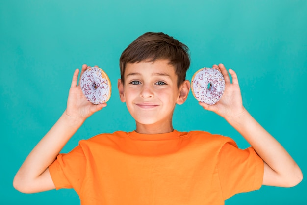 Little boy holding up two glazed doughnuts