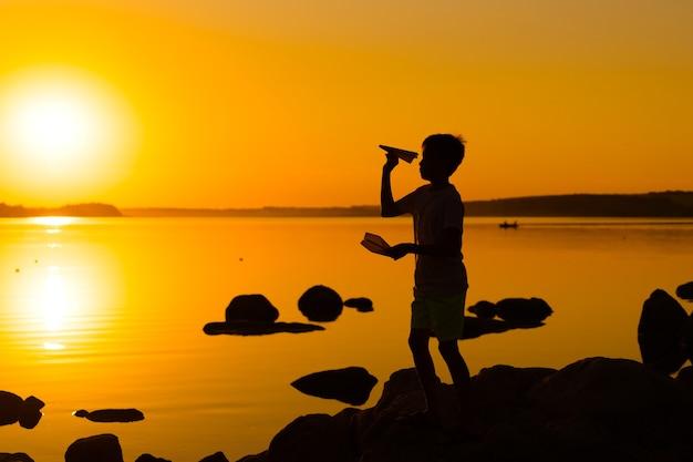 어린 소년은 일몰에 종이 비행기를 손에 들고 있습니다. 한 아이가 하늘을 향해 손을 들고 저녁에 호수에서 종이접기를 가지고 놀고 있습니다. 실루엣