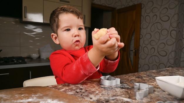어린 소년 그의 손에 반죽 조각을 보유