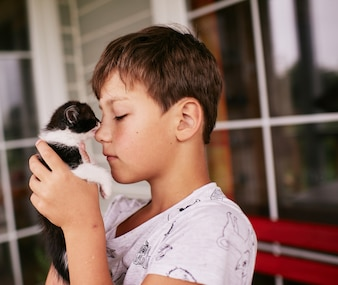 Little boy holds black and white kitty on his shoulder