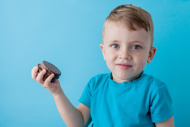 Little boy holds chocolate chip cookies