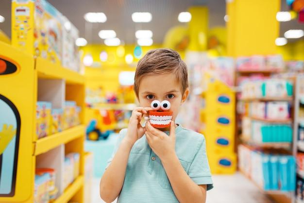 Маленький мальчик держит игрушку челюсти на полке в детском магазине, вид спереди.