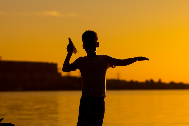 A little boy holds an origami in the form of an airplane in his hand and stands of the river at sunset.