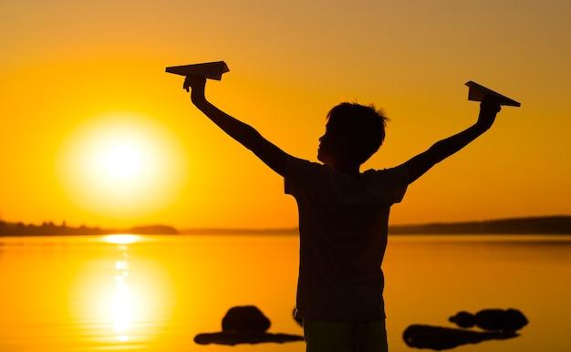 어린 소년은 일몰 때 두 대의 종이 비행기를 손에 들고 있습니다. 한 아이가 하늘을 향해 손을 들고 호수에서 저녁에 종이접기를 가지고 놀고 있습니다. 실루엣.