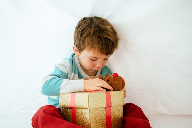 Little boy at home on christmas morning with gift