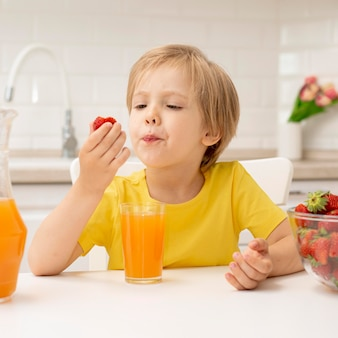 Little boy at home eating strawberry