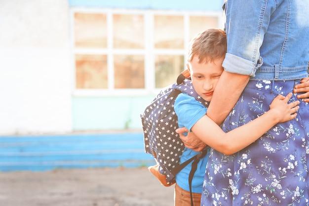 学校に行く前に母親を抱いて少年