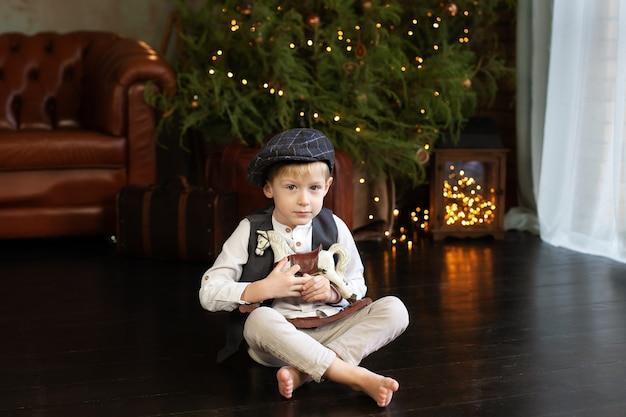 Маленький мальчик обнимает фигурку лошадки-качалки на рождество